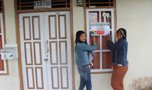 Winda Destriani (berjaket jeans) bersama Setiyo Rini menempelkan Lentera Perempuan di Kantor Desa Sumber Urip.
